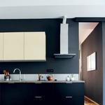 Kuhinja z minimalno opremo, ki pa je povsem funkcionalna. Namesto ploščic je lastnica izbrala pralno barvo. (foto: Mateja Jordović Potočnik)