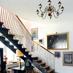 Spodnjo in zgornjo etažo združujejo orehove stopnice z ukrivljeno medeninasto ograjo. (foto: Mateja Jordović Potočnik)