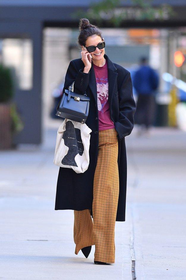 Široke kariraste hlače, T-majica in dolg plašč - kot nalašč za sprehod po mestu.